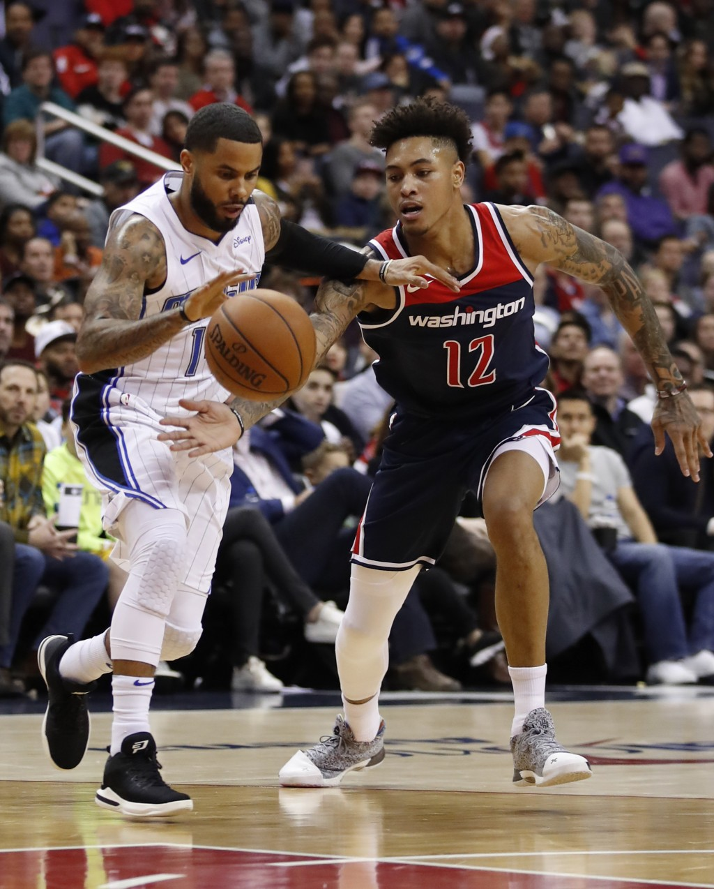 Orlando Magic guard D.J. Augustin, left, drives past Washington Wizards forward Kelly Oubre Jr., during the first half of an NBA basketball game Satur...