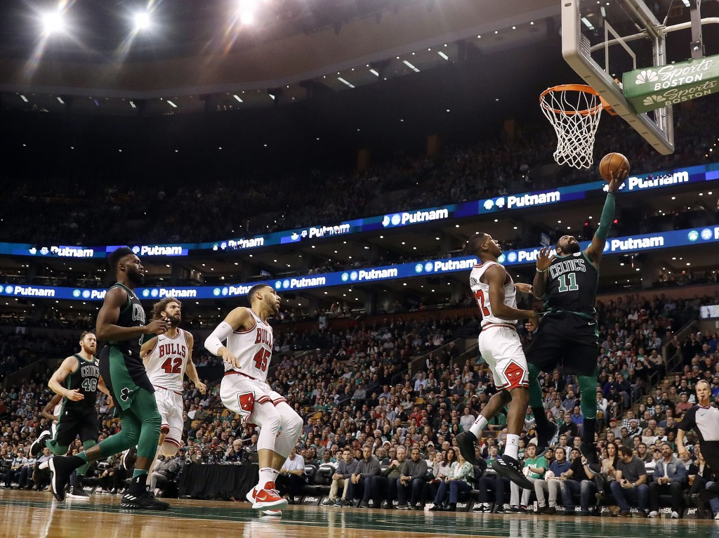 Boston Celtics guard Kyrie Irving goes in for a layup past Chicago Bulls' Kris Dunn during the first quarter of an NBA basketball game in Boston on Sa...