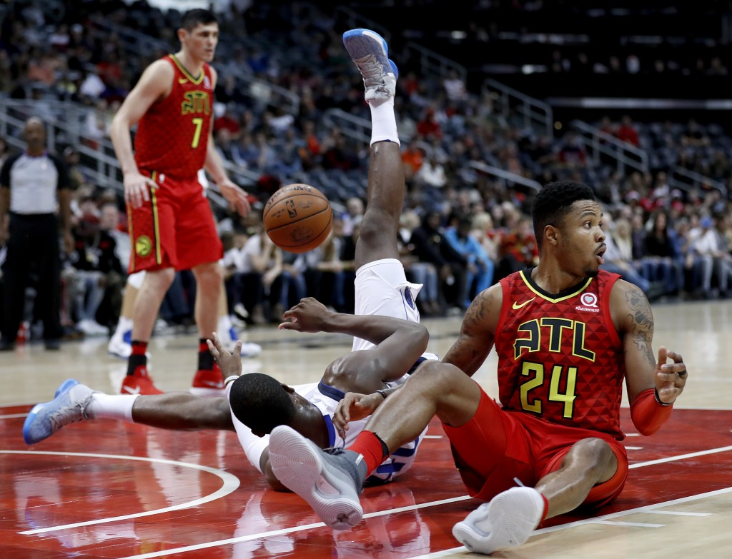 Atlanta Hawks' Kent Bazemore, right, reacts after being called for a foul while colliding with Dallas Mavericks' Harrison Barnes, center, in the fourt...
