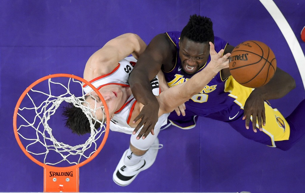 Portland Trail Blazers center Zach Collins, left, blocks a shot by Los Angeles Lakers forward Julius Randle during the second half of an NBA basketbal...