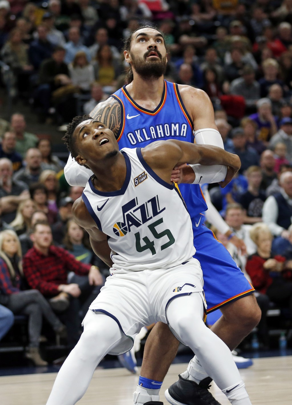 Utah Jazz guard Donovan Mitchell (45) and Oklahoma City Thunder center Steven Adams, right, battle under the boards for a rebound in the first half du...