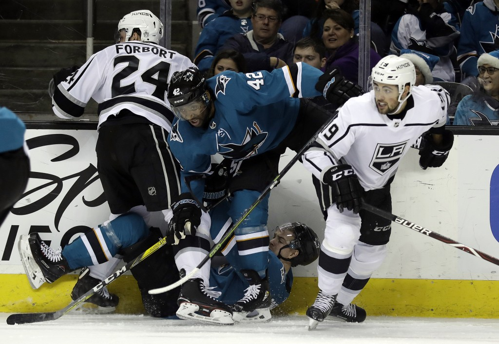 San Jose Sharks' Joel Ward (42) gets tangled against the boards with teammate Mikkel Boedker, bottom center, and Los Angeles Kings defenseman Derek Fo...