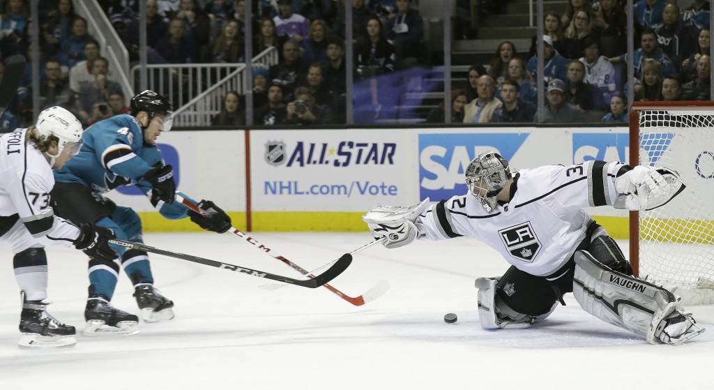 Los Angeles Kings goalie Jonathan Quick, right, stops a shot from San Jose Sharks center Tomas Hertl, center, during the first period of an NHL hockey...