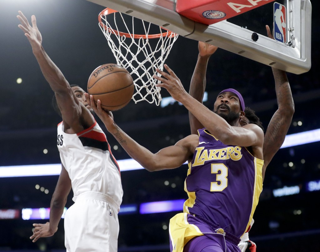 Los Angeles Lakers forward Corey Brewer, right, shoots around Portland Trail Blazers forward Maurice Harklessm during the first half of an NBA basketb...
