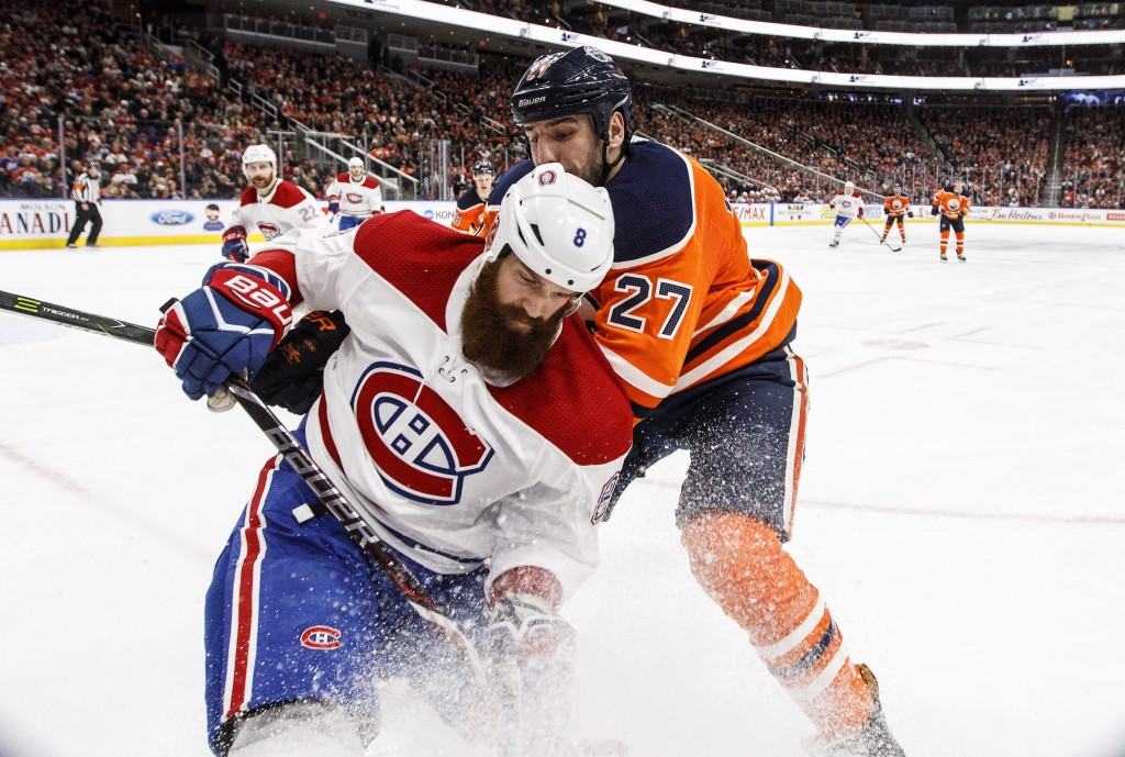 Montreal Canadiens Jordie Benn (8) and Edmonton Oilers' Milan Lucic (27) battle for the puck during second-period NHL hockey game action in Edmonton, ...