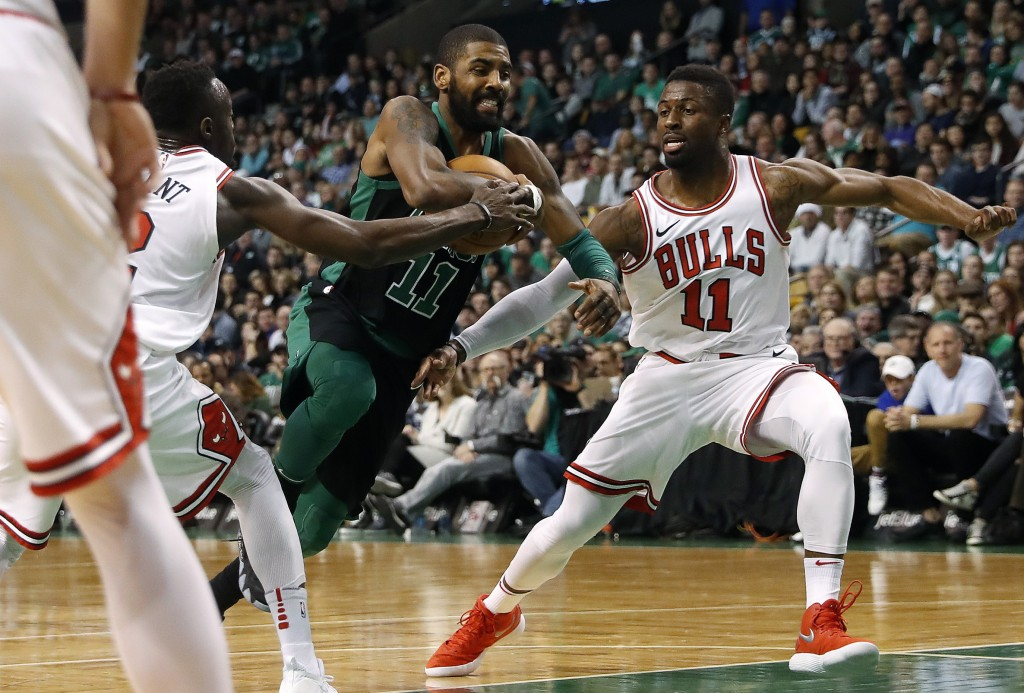 Boston Celtics' Kyrie Irving goes between Chicago Bulls' David Nwaba, right, and Jerian Grant during the second quarter of an NBA basketball game in B...
