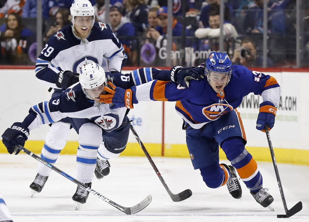 New York Islanders center Mathew Barzal (13) controls the puck against Winnipeg Jets center Andrew Copp (9) in the second period of an NHL hockey game...