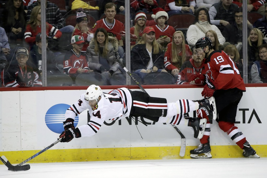 Chicago Blackhawks right wing Richard Panik (14), of Slovakia, dives for the puck as New Jersey Devils center Travis Zajac (19) loses his stick during...