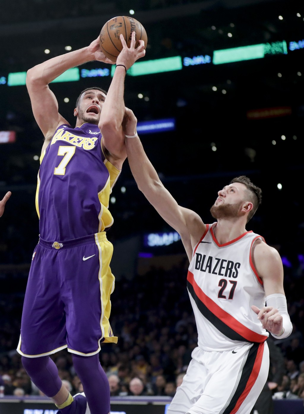 Los Angeles Lakers forward Larry Nance Jr., left, is fouled by Portland Trail Blazers center Jusuf Nurkic during the first half of an NBA basketball g...