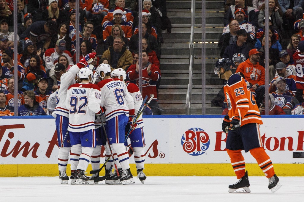 Montreal Canadiens, left, celebrate a goal as Edmonton Oilers' Darnell Nurse (25) skates past during second-period NHL hockey game action in Edmonton,...
