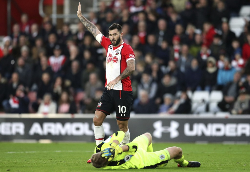 Southampton's Charlie Austin gestures as Huddersfield Town goalkeeper Jonas Lossl lies injured during the English Premier League soccer match between ...