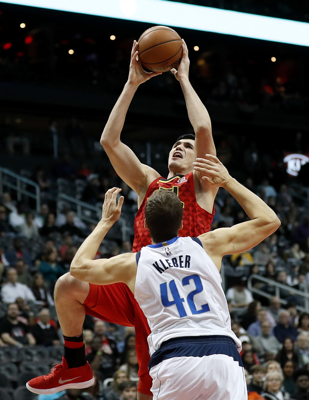Atlanta Hawks' Ersan Ilyasova, top, of Turkey, shoots against Dallas Mavericks' Maximilian Kleber, of Germany, in the first quarter of an NBA basketba...