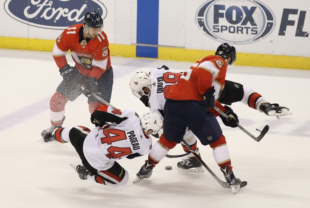 Florida Panthers' Jonathan Huberdeau (11) and Aleksander Barkov, right, of Finland, look for the puck as Ottawa Senators' Jean-Gabriel Pageau (44) and...