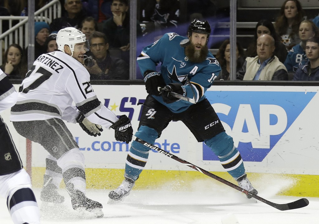 San Jose Sharks center Joe Thornton, right, passes as Los Angeles Kings defenseman Alec Martinez (27) closes in during the first period of an NHL hock...