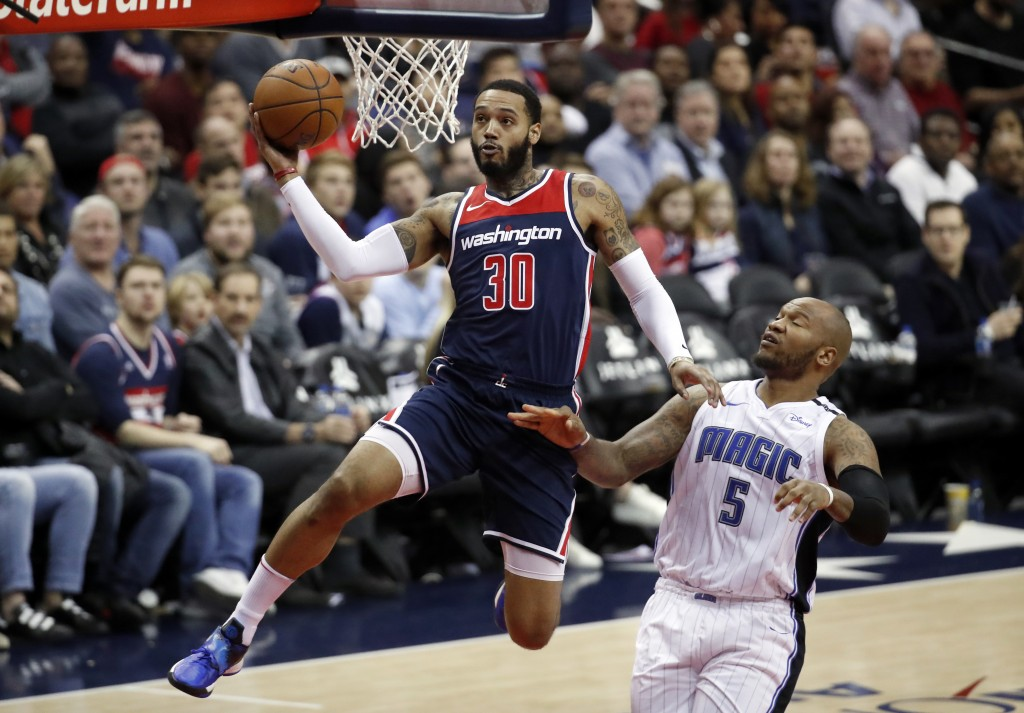 Washington Wizards forward Mike Scott (30) drives past Orlando Magic forward Marreese Speights (5) for a shot during the second half of an NBA basketb...