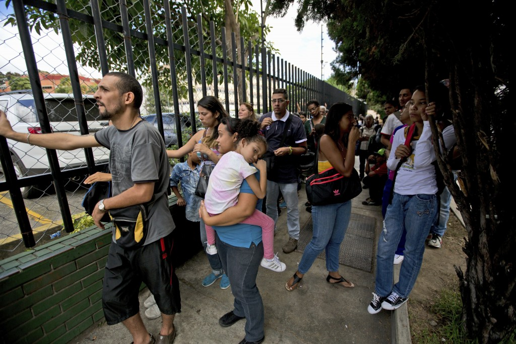 In this Dec. 22, 2017 photo, locals line up outside a mall to buy discounted toys and shoes, in Caracas, Venezuela. Water rationing is common, and a m...