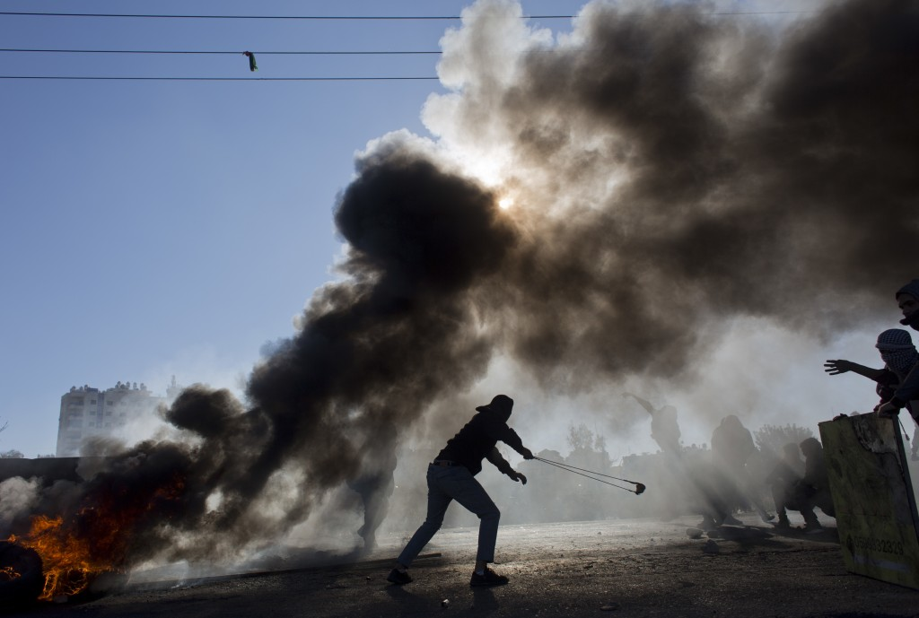 Palestinian protesters burn tires and clash with Israeli troops following protests against U.S. President Donald Trump's decision to recognize Jerusal...