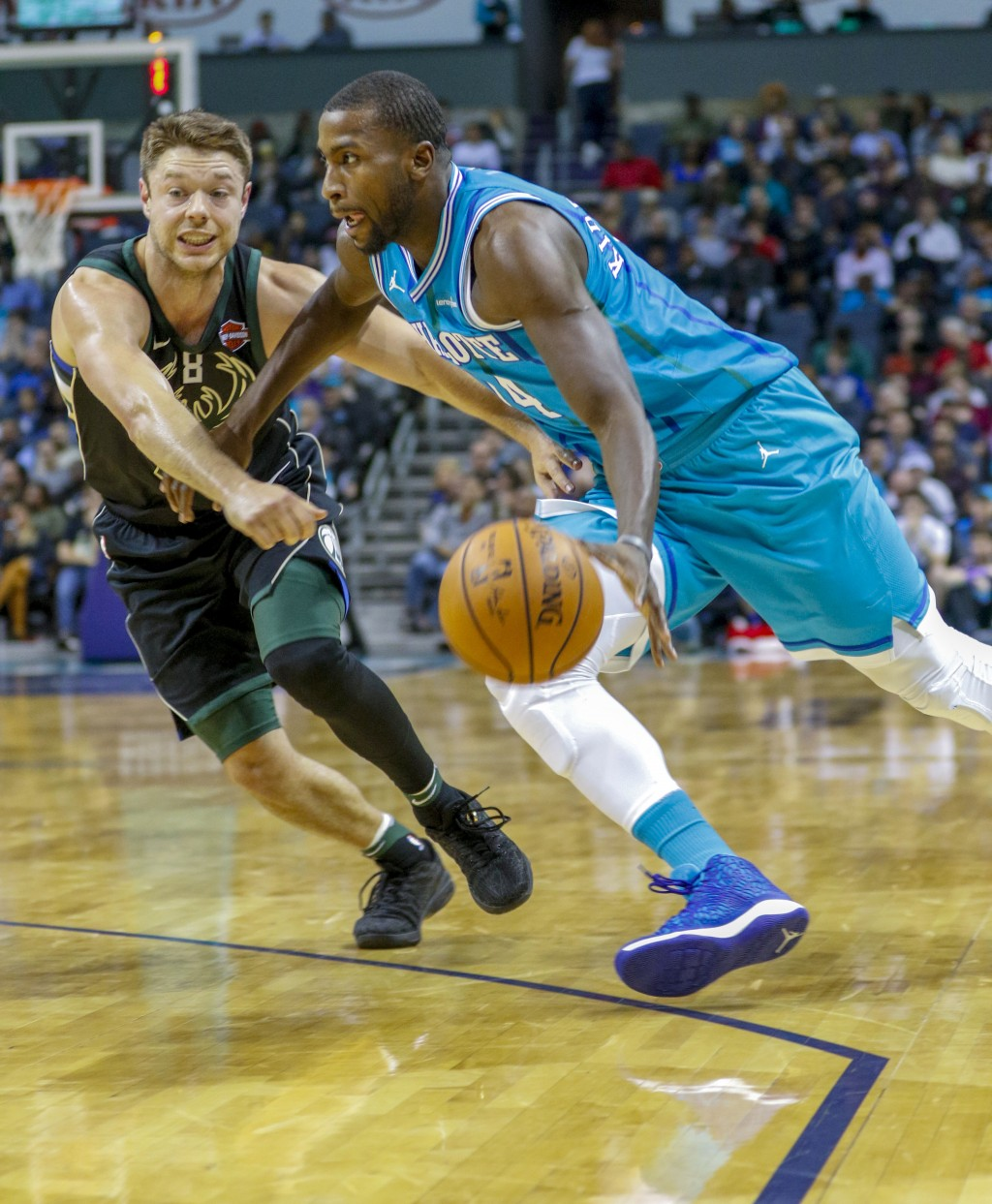 Charlotte Hornets forward Michael Kidd-Gilchrist, right, drives against Bucks guard Matthew Dellavedova, of Australia, in the first half of an NBA bas...