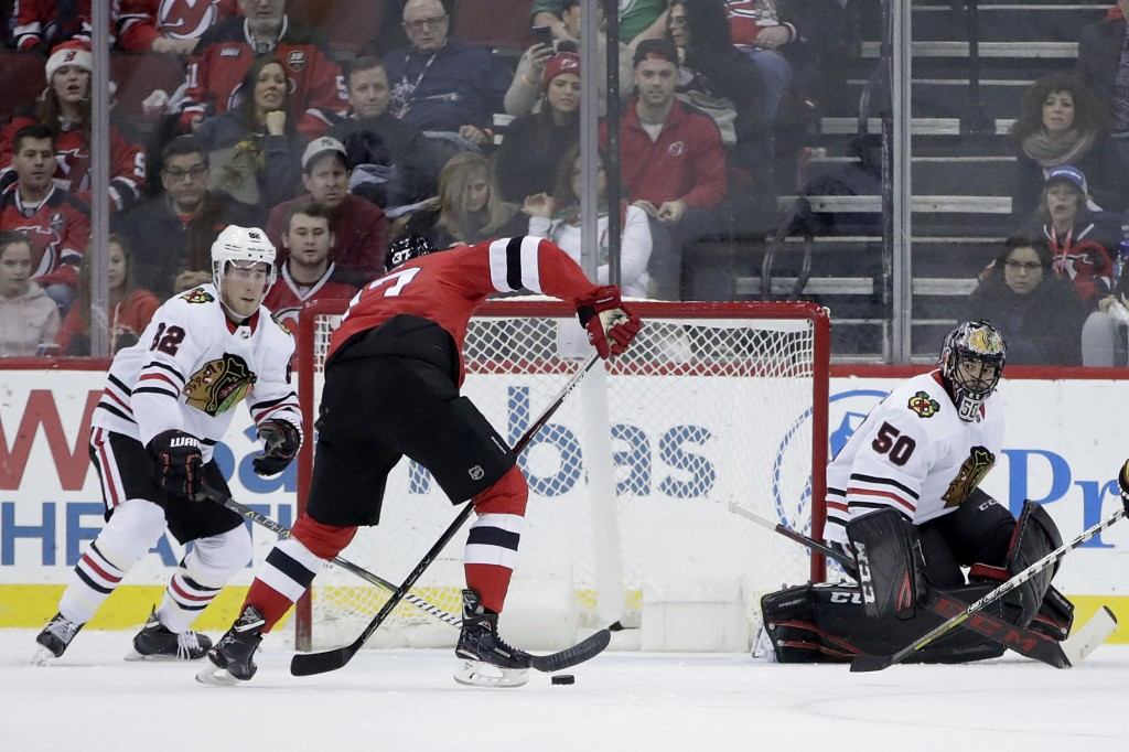 New Jersey Devils center Pavel Zacha, second from left, of the Czech Republic, prepares to shoot for a goal as Chicago Blackhawks goalie Corey Crawfor...