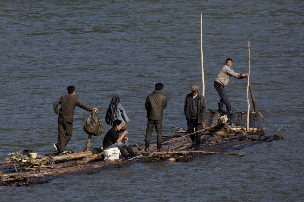 In this Aug. 30, 2017 photo, North Korean men ride a makeshift raft made of fastened logs down the Yalu river that divides North Korea from the Chines...