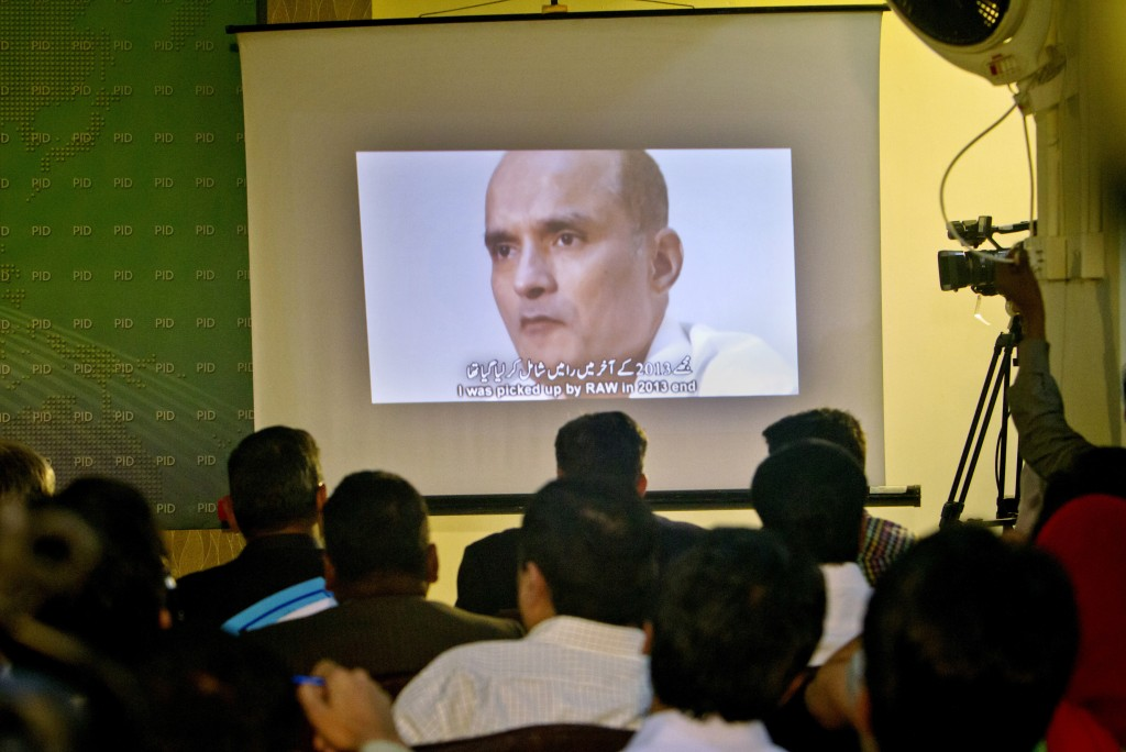 FILE - In this March 29, 2016, file photo, journalists look a image of Indian naval officer Kulbhushan Jadhav, who was arrested in March 2016, during ...