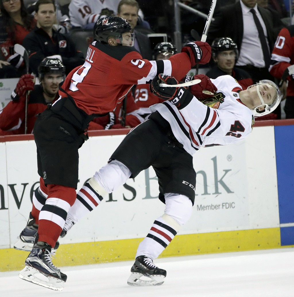 New Jersey Devils left wing Taylor Hall, left, hits Chicago Blackhawks defenseman Gustav Forsling (42), of Sweden, during the second period of an NHL ...