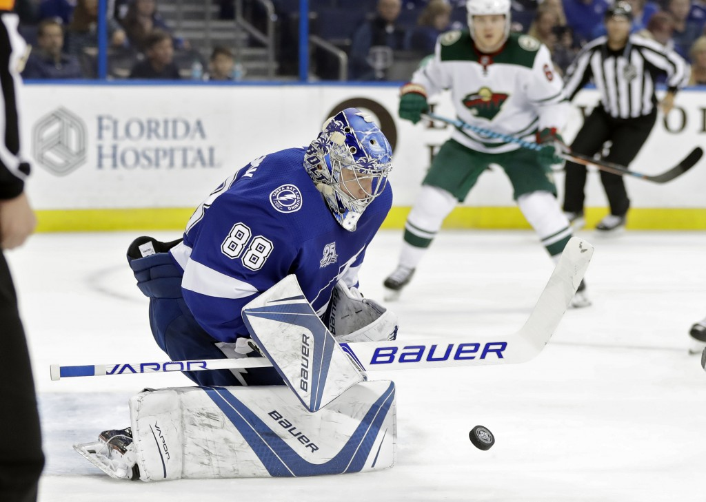 Tampa Bay Lightning goalie Andrei Vasilevskiy (88) makes a save on a shot by the Minnesota Wild during the first period of an NHL hockey game Saturday...