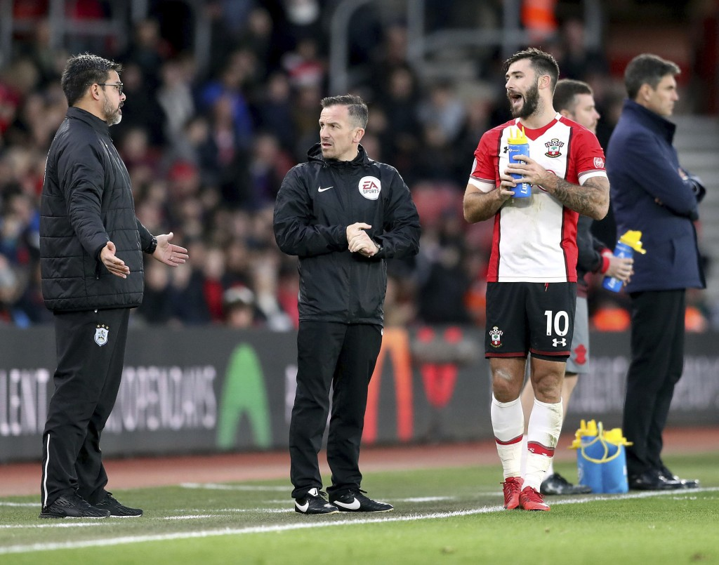 Southampton's Charlie Austin, right, argues with Huddersfield Town manager David Wagner, left, about goalkeeper Jonas Lossl's injury, during the Engli...