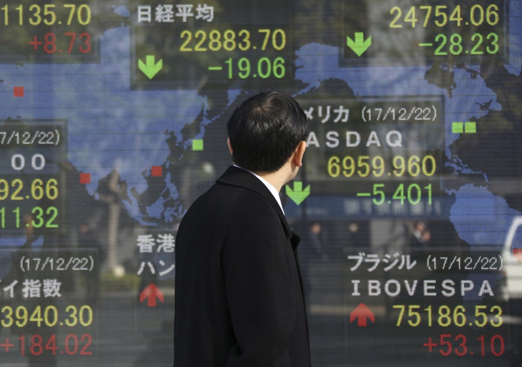 A man looks at an electronic stock board of a securities firm in Tokyo, Monday, Dec. 25, 2017. Shares were lower in quiet trading Monday in the few As...