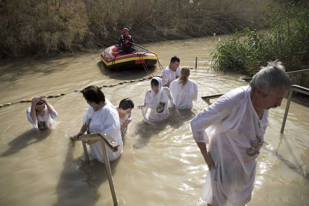 In this Wednesday, Jan. 18, 2017 photo, Christian Orthodox pilgrims immerse themselves into the waters of the Jordan River during a baptism ceremony a...