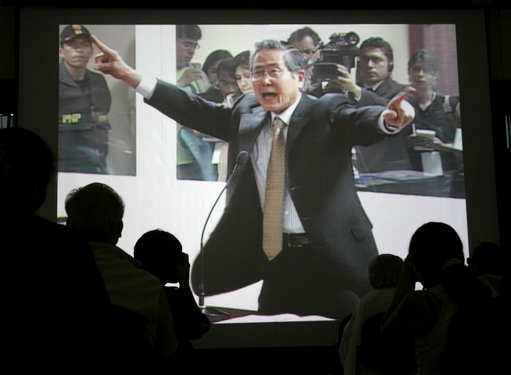 FILE - In this Dec. 10, 2007 file photo, journalists watch a screen showing live images of Peru's former President Alberto Fujimori during the first d...