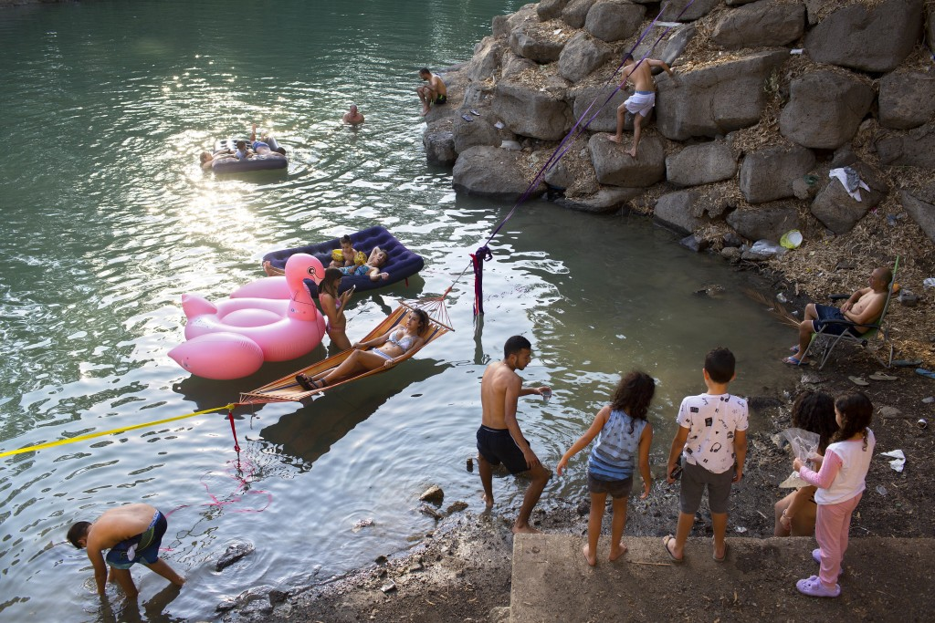 In this Wednesday, Oct. 11, 2017 photo, Israelis camp out on the banks of the Jordan River, where the Sea of Galilee flows into the river, near the no...