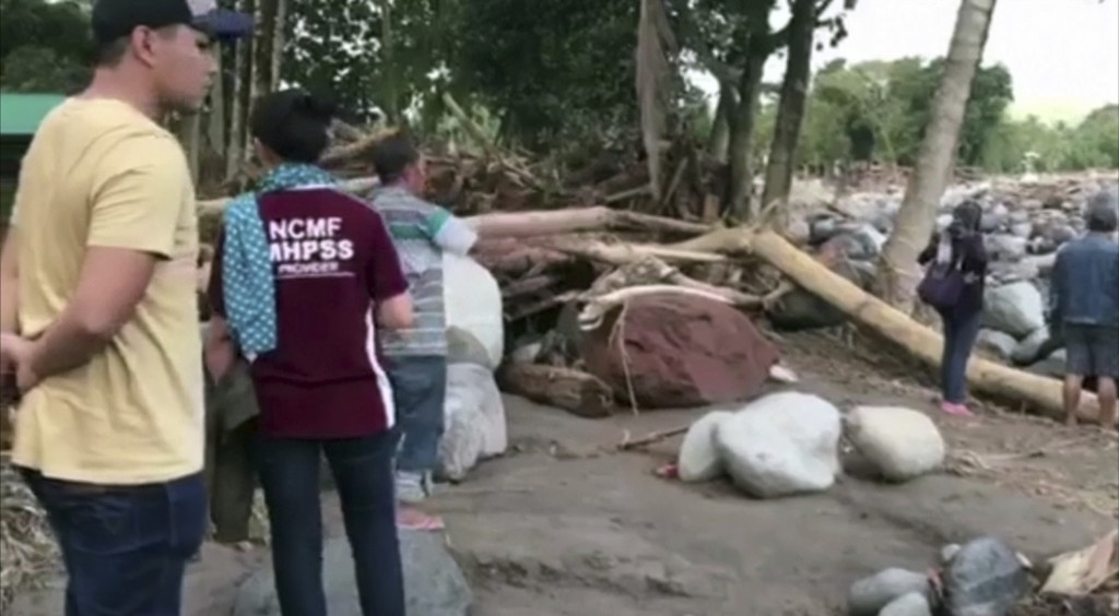 In this image made from video, people look for bodies amid debris, broken branches on devastated beach in Lanao del Norte, southern Philippines Monday...