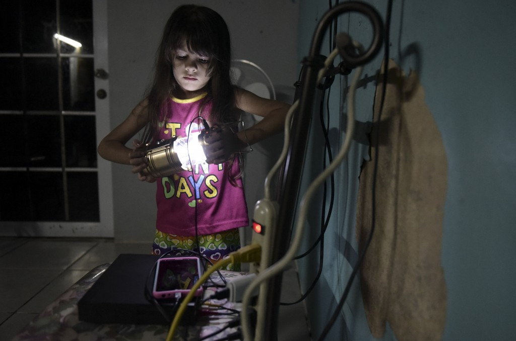 In this Dec. 21, 2017 photo, six year old Melanie Oliveras Gonzalez holds a lantern in the living room of her house in Sector Padre Ibañes, in Morovis...