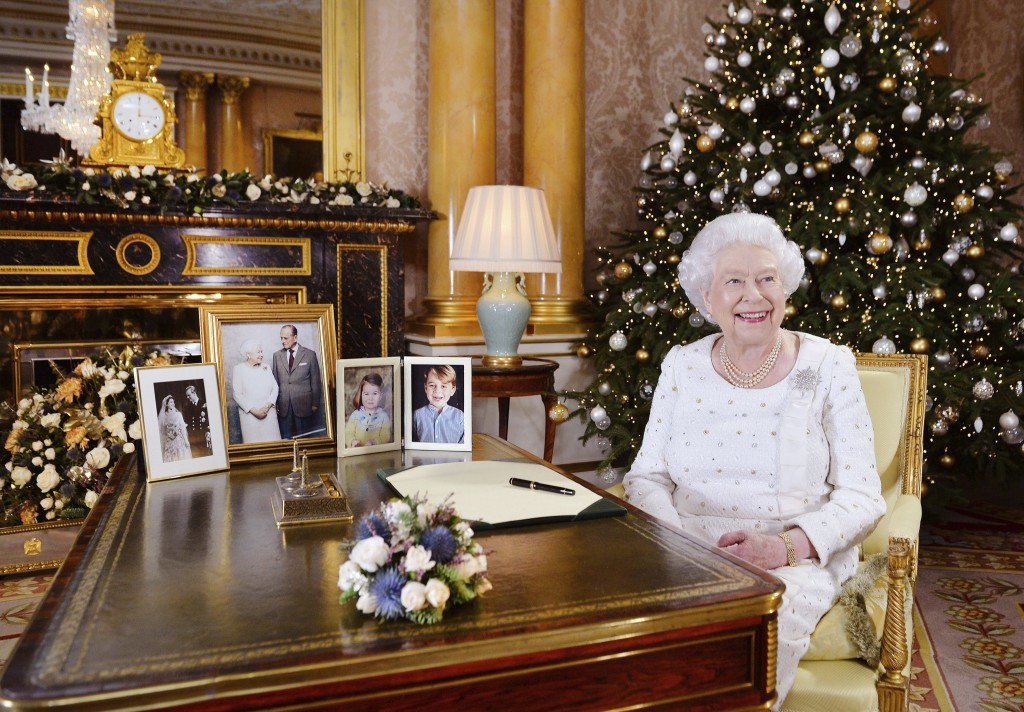 In this photo released on Monday, Dec. 25, 2017, Britain's Queen Elizabeth sits at a desk in the 1844 Room at Buckingham Palace, after recording her C...
