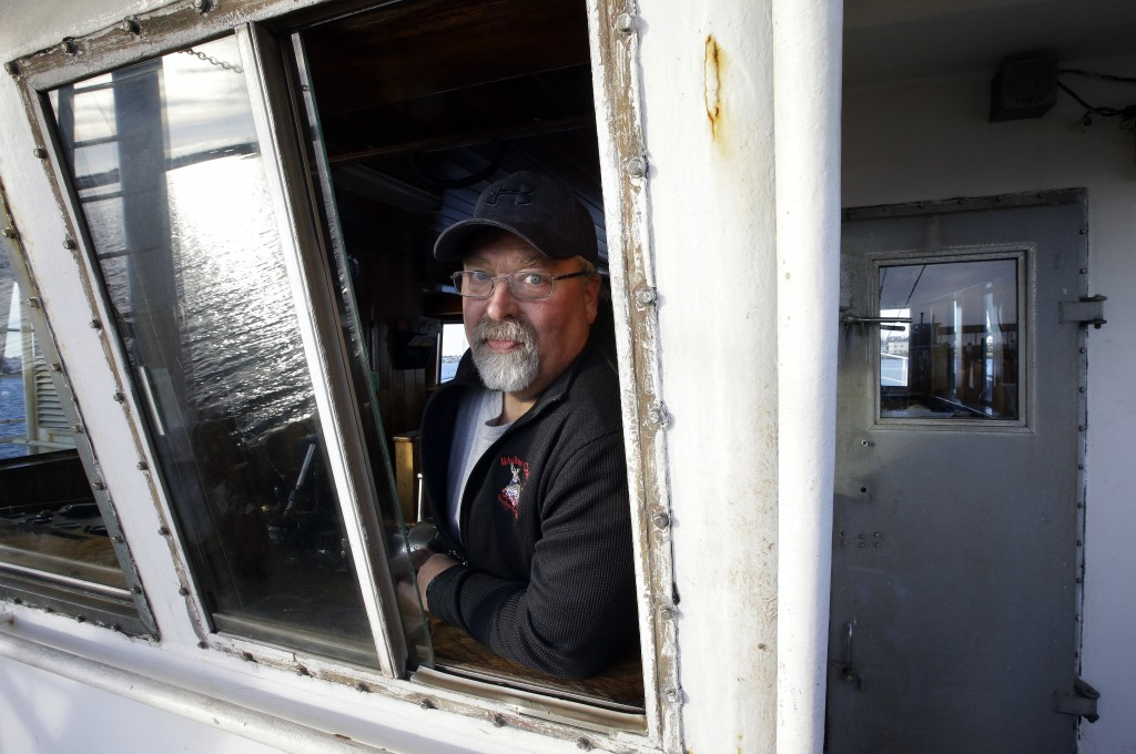 "In this Wednesday, Dec. 6, 2017 photo scallop fisherman Eric Hansen, of Marion, Mass., stands for a photo aboard his fishing vessel ""Endeavor,"" in Fai..."