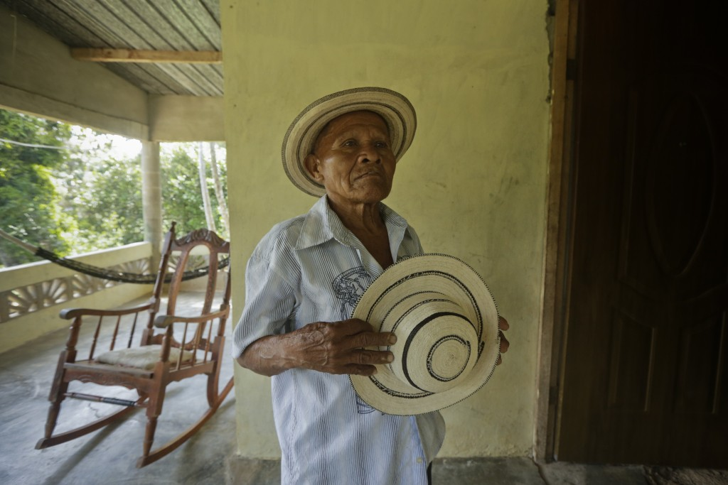 In this Dec. 16, 2017 photo, Pasion Gutierrez, 81, holds a finished traditional Panamanian pintao hat at his home in El Jaguito, Panama. The round hat...