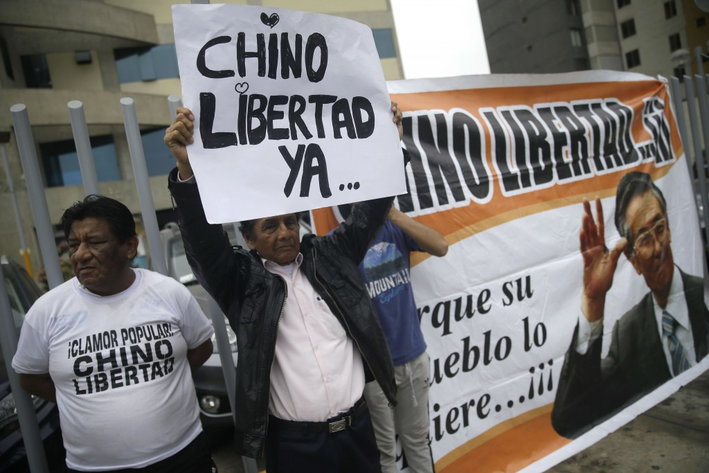 """A supporter of former President Alberto Fujimori stands with poster that says in Spanish """"Free Chino now"""" outside the clinic where the jailed leader w..."""
