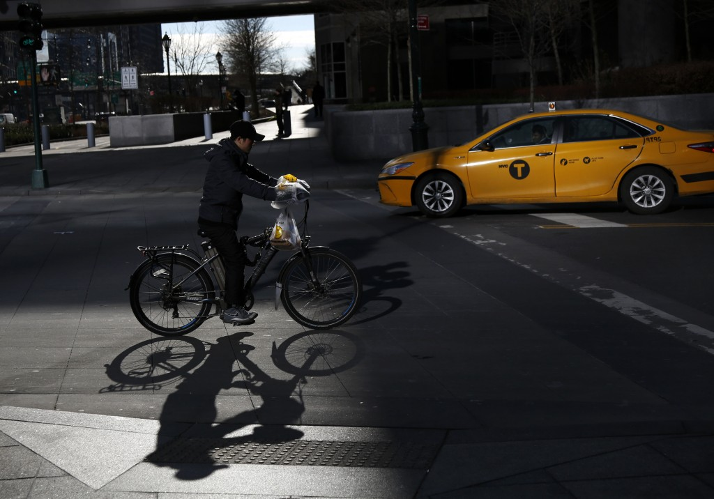 In this Thursday, Dec. 21, 2017 photo, a man making deliveries rides an electronic bike in New York. A plan to intensify a crackdown on electric bicyc...