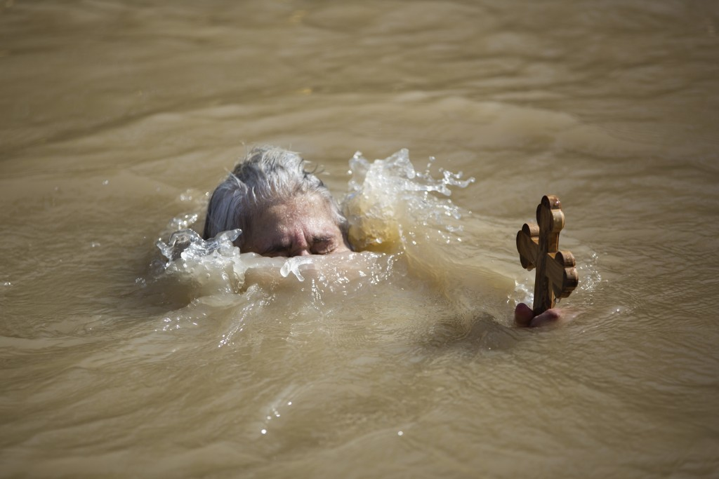 In this Wednesday, Jan. 18, 2017 photo, a Christian Orthodox pilgrim immerses herself into the waters of the Jordan River during a baptism ceremony as...