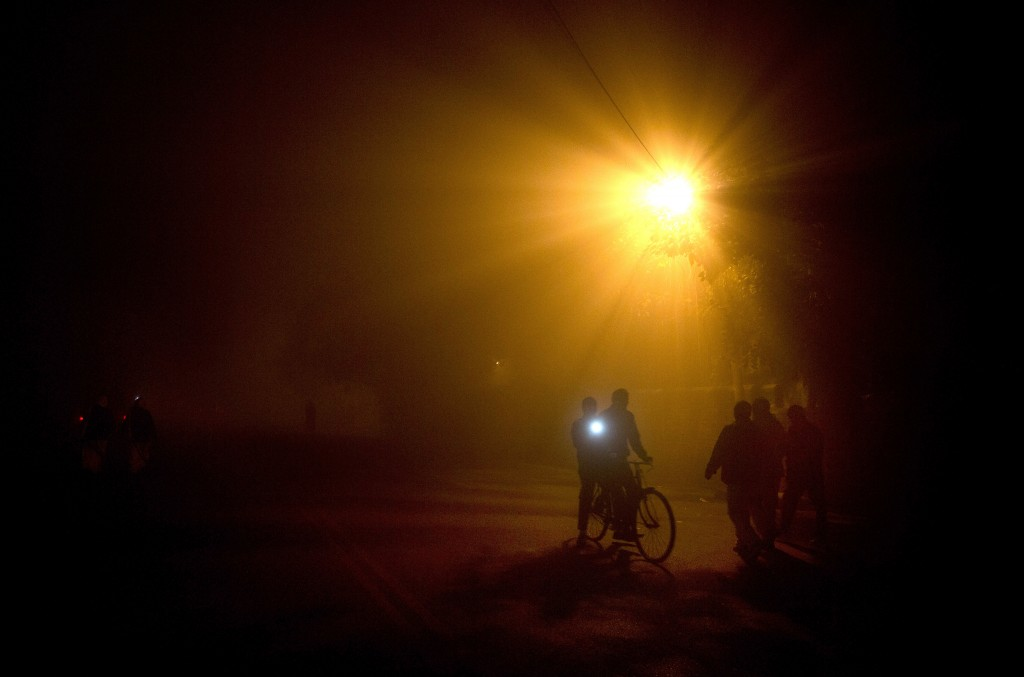 In this Dec. 25, 2017, file photo, a cyclist uses a flashlight to see the road as he rides in thick fog in Lucknow, India. In the winter months, north...