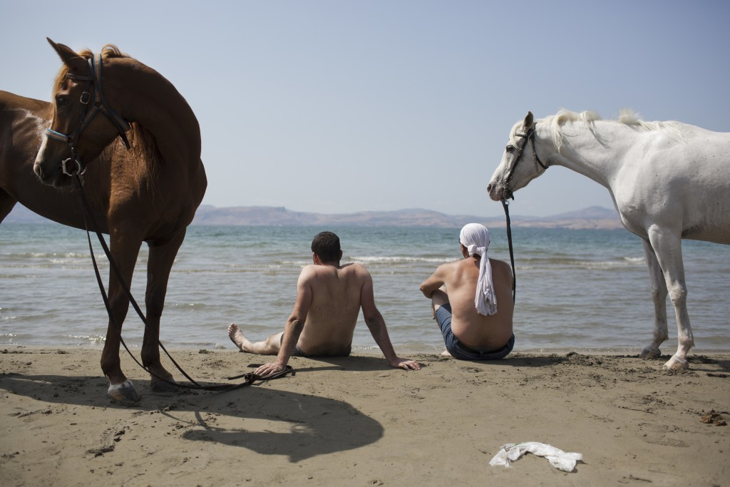 In this Saturday, Sept. 23, 2017 photo, Israeli Druse men sit with their horses on the shores of the Sea of Galilee near the northern Israeli Kibbutz ...