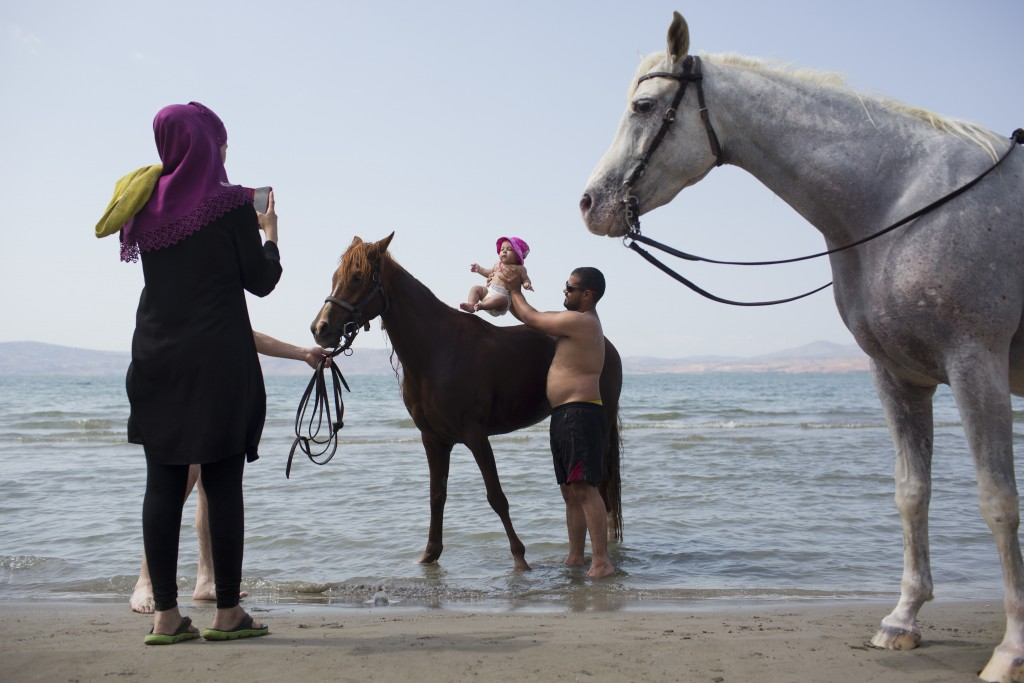 In this Saturday, Sept. 23, 2017 photo, Israeli Arabs take a picture of their baby with horses in the Sea of Galilee near the northern Israeli Kibbutz...