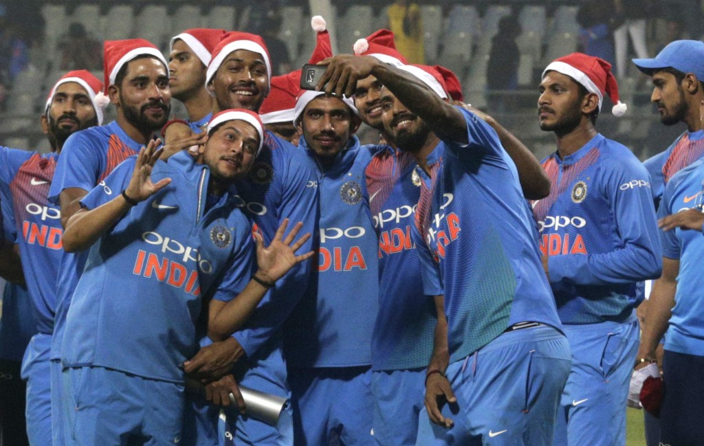In this Dec. 24, 2017, file photo, India's Lokesh Rahul, third right, takes a selfie with teammates wearing Santa caps after their win in the third Tw...