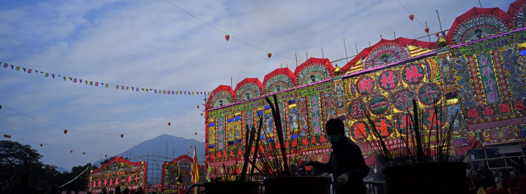 In this Dec. 10, 2017 photo, a villager burns incense in front of a huge bamboo theater with traditional decorations during the Tai Ping Ching Jiu fes...