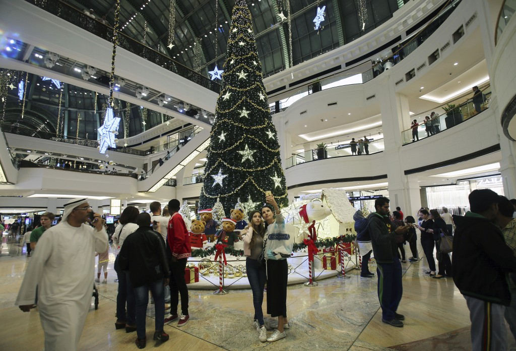 In this Wednesday, Dec. 20, 2017 photo, people take selfie with a giant Christmas tree at a shopping mall in Dubai, United Arab Emirates. Residents in...