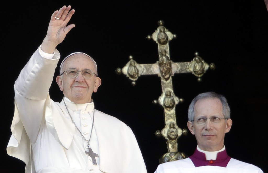Pope Francis, flanked by Master of Ceremonies Bishop Guido Marini, waves to faithful during the Urbi et Orbi (Latin for ' to the city and to the world...
