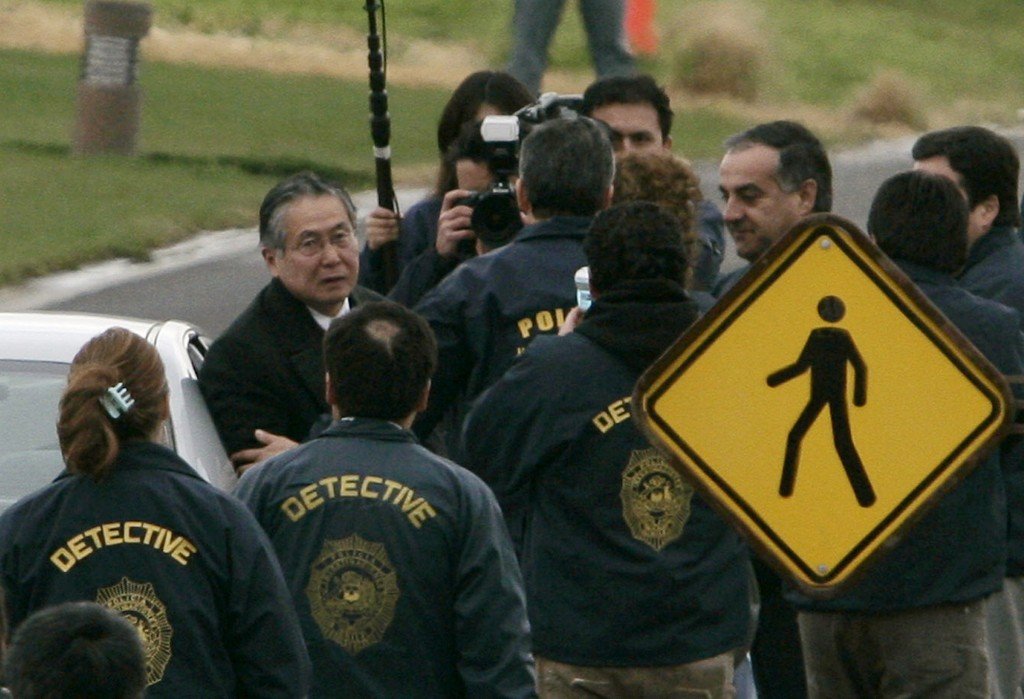 FILE -  In this Sept. 22, 2007 photo, Chilean police surround Peru's former President Alberto Fujimori as he leaves his home in Santiago to be extradi...
