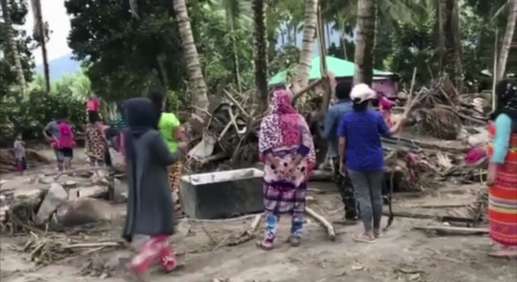 In this image made from video, people look for bodies amid debris and broken branches on devastated beach in Lanao del Norte, southern Philippines Mon...