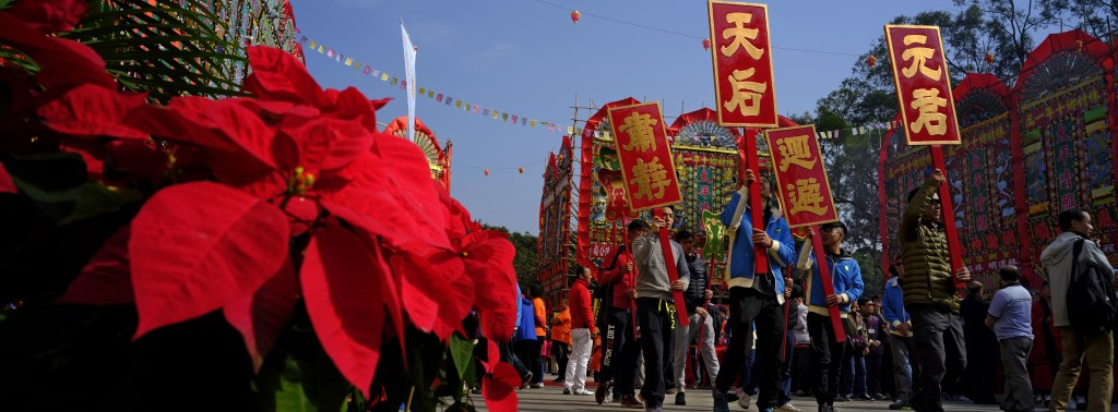 In this Dec. 10, 2017 photo, villagers raise wooden signs as they march past some Christmas flowers in front of a huge bamboo theater with traditional...